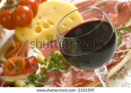 glass of red wine close up with food in background - stock photo
