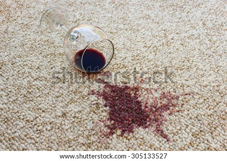 glass of red wine fell on carpet - stock photo