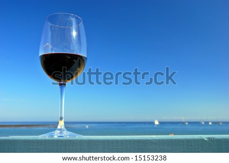 Glass of red wine on a restaurant's deck railing by the ocean beach - stock photo