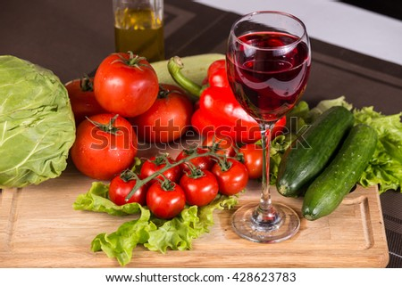 Glass of red wine on the table near fresh salad vegetables - stock photo