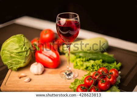 Glass of red wine on the table near fresh salad vegetables - close up blurred photo - stock photo