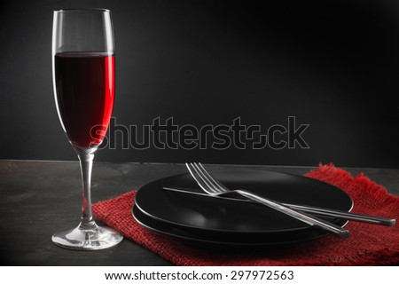 Glass of red wine, plates, silverware and napkin on dark wooden table. - stock photo