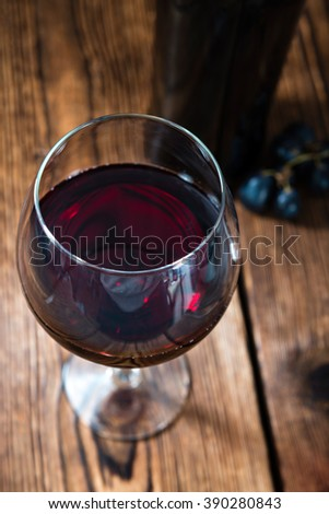 Glass of Red Wine (selective focus) on an old rustic wooden table - stock photo