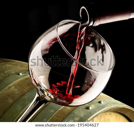 glass of red wine with barrel - stock photo