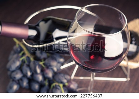 Glass of red wine with bottle and grapes. Winery background toned image - stock photo