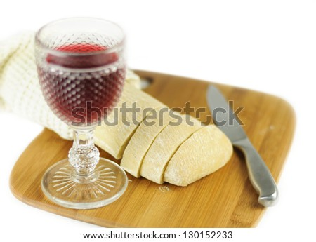 Glass of red wine with bread and knife on the cutting board - stock photo