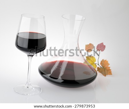 Glass of red wine with carafe - stock photo