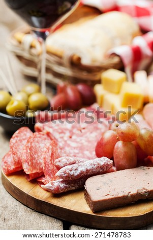Glass of red wine with charcuterie assortment on the background - stock photo