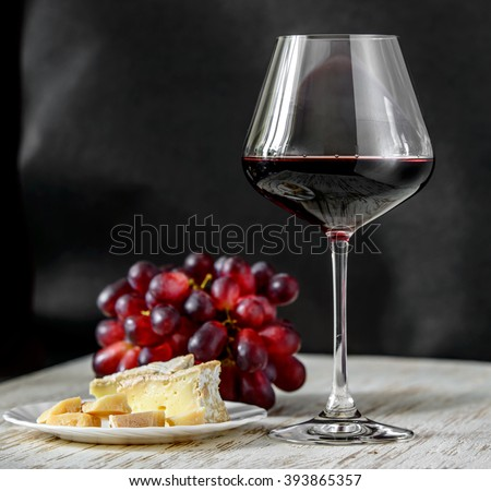 Glass of red wine with cheese and grapes on a white table and black background. - stock photo