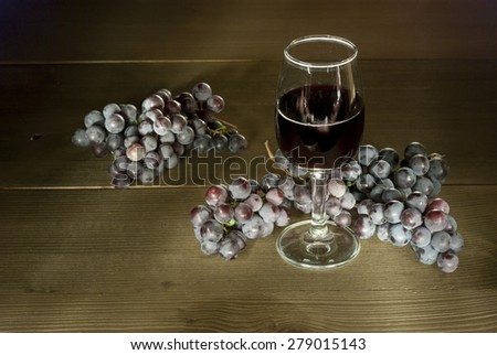 glass of red wine with clusters of grapes on wooden table - stock photo