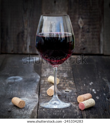 Glass of red wine with corks on old wooden table - stock photo