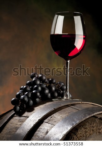 glass of red wine with grapes and old barrel - stock photo