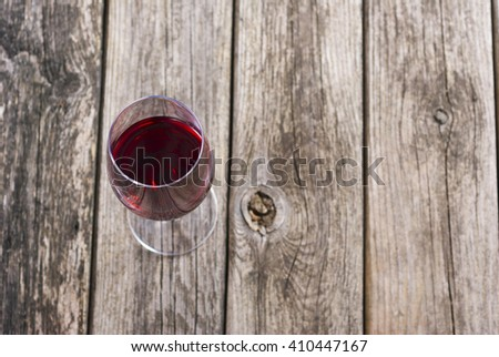 glass of red wine with grapes on rusty wooden table - stock photo