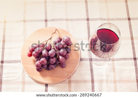 Glass of red wine with red globe grapes  photographed onthe table with natural light - stock photo