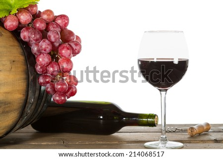 Glass of red wine with some grapes and oak barrels - stock photo