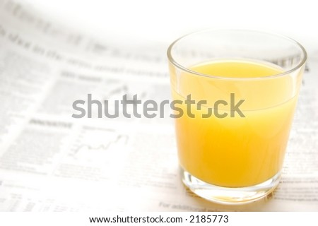 Glass of refreshing orange fruit juice over out of focus business paper with graphs, macro - stock photo