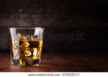 Glass of scotch whiskey and ice - stock photo