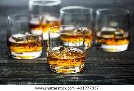 Glass of scotch whiskey and ice on a black wooden background,selectiv focus - stock photo
