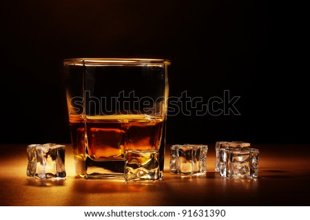 glass of scotch whiskey and ice on wooden table on brown background - stock photo
