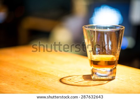 Glass of scotch whiskey on wooden background with copyspace - stock photo