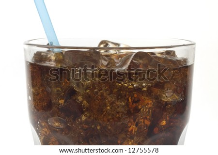 Glass of soda with a straw against white close-up of top - stock photo