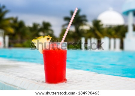 Glass of Strawberry Daiquiri cocktail standing on the swimming pool ledge in an tropical resort - stock photo