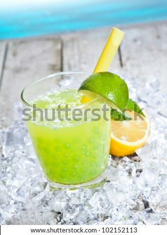 Glass of tangy refreshing lime boba tea cocktail standing on a bed of crushed ice on a wooden deck alongside blue water - stock photo