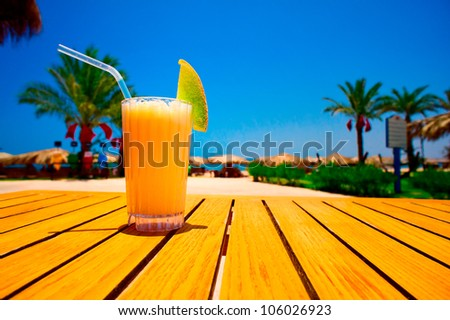 Glass of tasty juice with pipe on the table next to beach. Egypt. - stock photo