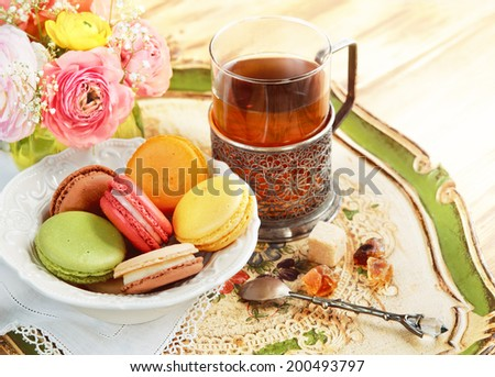 Glass of tea with macaroons on a table with spring flowers - stock photo