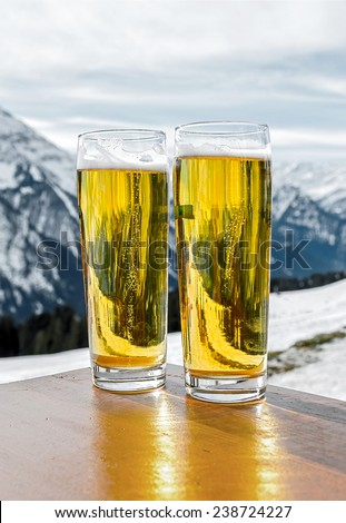 Glass of the fustrian beer against snow mountains a valley of the Zillertal - Mayrhofen, Austria - stock photo