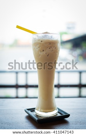 Glass of thick creamy coffee milkshake, frappe or iced coffee with a topping of ice cream and drizzled syrup on an old wooden table - stock photo