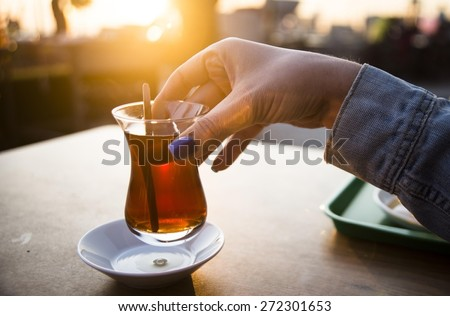 Glass of Turkish tea on the table.Sunset background. - stock photo
