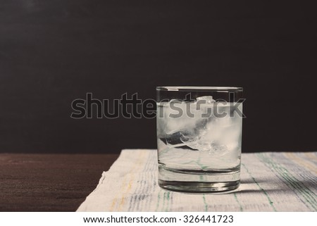 Glass of vodka on the rocks. Vintage style. Toned image. - stock photo