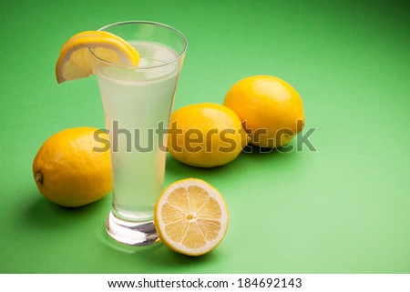 Glass of water and fresh lemon on a green background - stock photo
