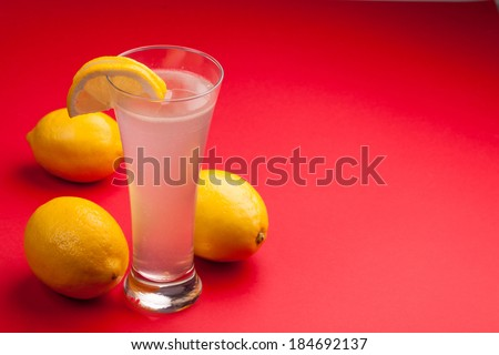 Glass of water and fresh lemon on a red background - stock photo