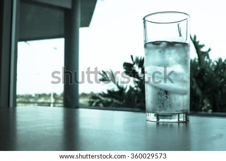 Glass of water and ice on the table - cold filter - stock photo