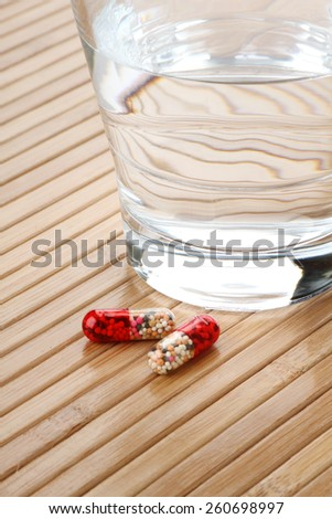 Glass of Water and Medicine Capsules - stock photo