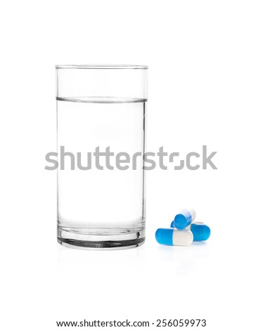 Glass of water and pill and capsules on white background - stock photo