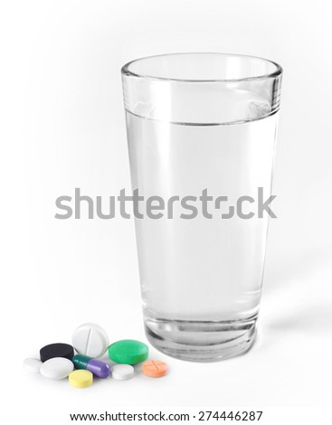 Glass of water and pills on a light background - stock photo