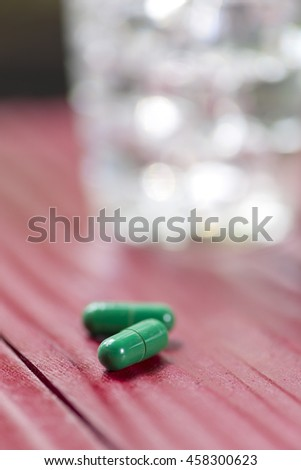 Glass of water and pills.Selective focus. - stock photo