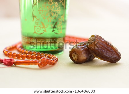 Glass of water,dates and rosary. - stock photo