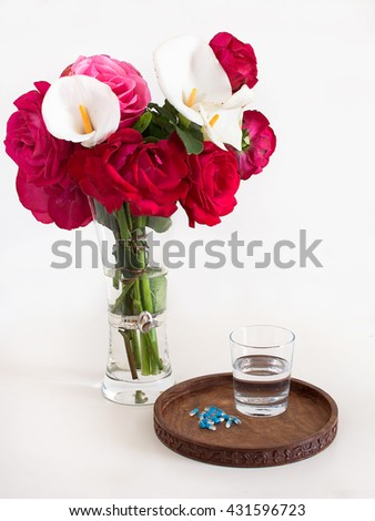 glass of water, medicines, flowers and wooden tray - stock photo
