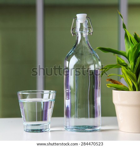 Glass of water with a bottle on table - stock photo
