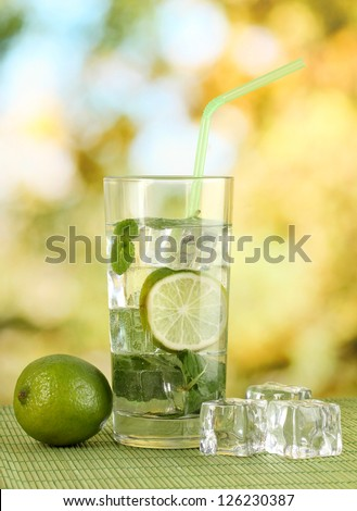Glass of water with ice, mint and lime on table on bright background - stock photo