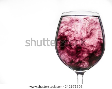 glass of water with injected ink rotating in confused cloud - stock photo