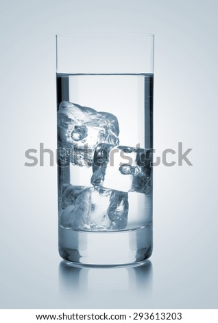 Glass of water with three ice cubes over blue gradient background - stock photo