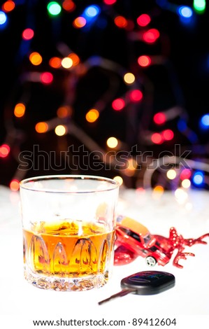 Glass of whiskey, a car key and a toy car over a reindeer with lights at the background - stock photo