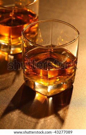 Glass of whiskey and ice on brown bar counter - stock photo