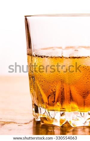 Glass of whiskey and ice on white background - stock photo