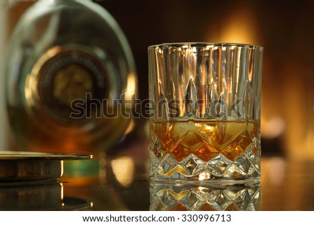Glass of whiskey and whiskey bottle  / whiskey on the rocks/ cognac glass/ brandy glass / rum glass - stock photo